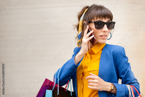 Young girl speaks on the phone while shopping on a bright background Slika na platnu