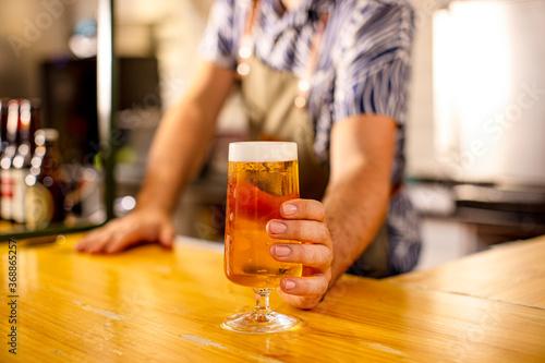 Fototapeta bartender serving a beer at the bar counter