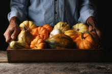 Farmer At His Stand Holding A Wood Crate Of Autumn Vegetables And Decorative Gourds And Pumpkins, With Warm Side Light.