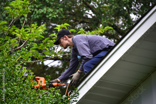 Cutting Limbs From Roof Top Canvas Print