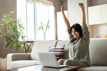 Excited Indian Woman Celebrating Online Win Success Looking At Laptop At Home. Happy Euphoric Indian Lady Student, Lottery Winner Raising Hands Get New Job Opportunity, Watching Game On Computer.