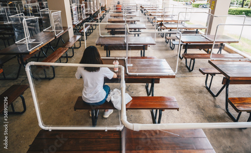 Obraz Rear view of woman sitting on wooden table with group of plastic partition setting on table in canteen for reduce and protection the COVID-19 virus spreads in pandemic. - fototapety do salonu