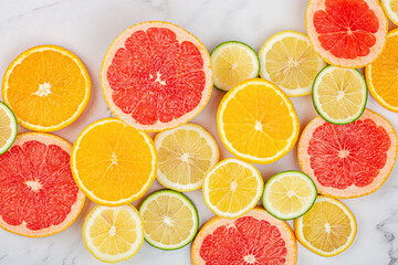Creative background made of summer tropical fruits with grapefruit, orange, tangerine, lemon, lime on white marble background. Food concept. Flat lay, top view, copy space, mockup