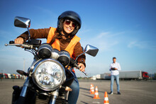 Female Student With Helmet Taking Motorcycle Lessons And Practicing Ride. In Background Traffic Cones And Instructor With Checklist Rating And Evaluating The Ride. Motorcycle School Of Driving.