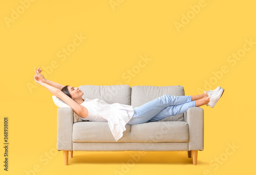 Young woman relaxing on sofa against color background Fotobehang