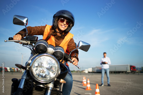 Female student with helmet taking motorcycle lessons and practicing ride Fototapeta