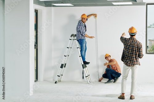 Obraz Team of construction workers in hardhats measuring wall with tape measure - fototapety do salonu