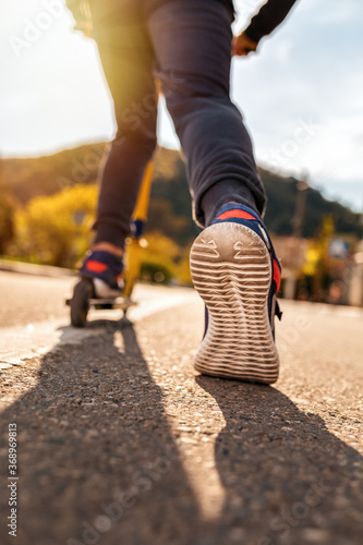 A teenage boy rides a scooter. Right foot in a sneaker close-up. Bottom and rear view. Empty street in Sunny weather in the background. Concept of youth activity, sports and recreation