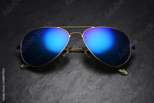 Fotografia Blue mirror aviator sunglasses on black slate background