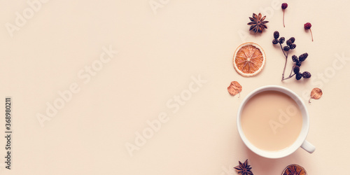 Autumn pastel background. A cup of hot coffee or tea with milk with autumn leaves and anise. Banner with copy space for text. Flat lay, top view.