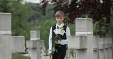 Teenager Boy Coming To Honour His Perished Father At Cemetery. Young Kid Walking And Putting White Lily Flower On Gravestone Of His Dad American Soldier. Concept Of Memorial Day