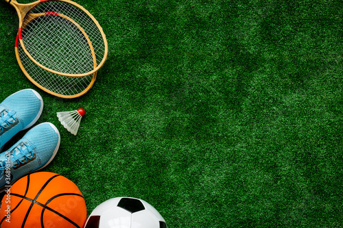 Flat lay of sport balls - football, basketball on grass. Top view copy space