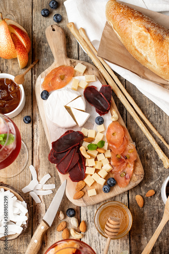 Wooden board with different types of cheeses, meats, fruits, nuts, baguette on a wooden table.Rustic style.French tasting party. © Юлия Усикова