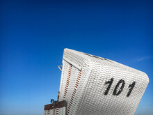 Traditional North German White Beach Chair With Black Number 101 At North Sea Beach Against Blue Sky