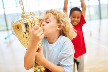 Boy Kissing Golden Trophy While Standing In School Gym
