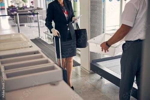 Elegant businesswoman passing through luggage control in airport Fototapet