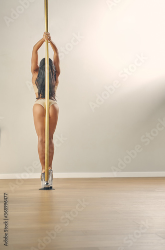 Valokuvatapetti Sexy young woman in lingerie posing in pole dance studio