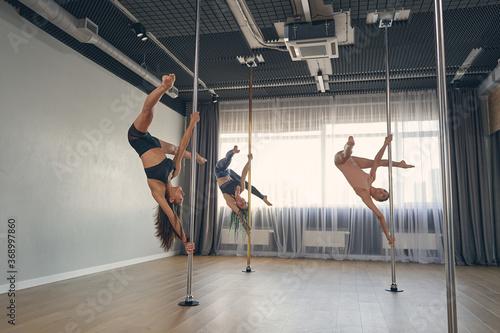 Fotografija Three beautiful young women performing pole dance tricks