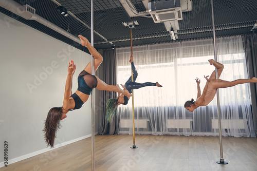 Obraz na plátně Beautiful female dancers performing pole dance tricks