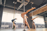 Beautiful female dancers performing pole dance tricks in studio
