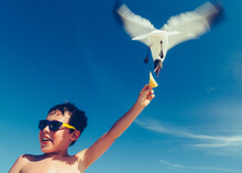 Low Angle View Of Shirtless Man Feeding Bird Against Blue Sky