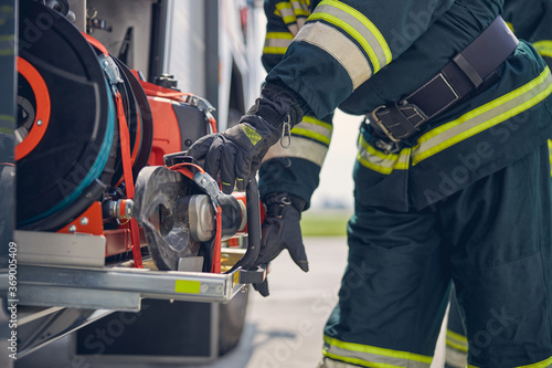 Portrait of firefighter wearing protective gloves working on fire engine Canvas Print