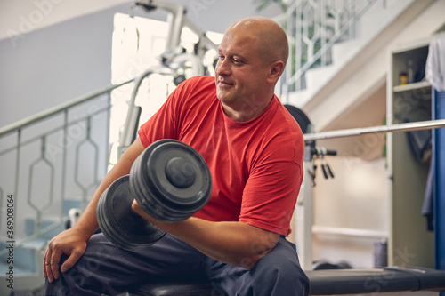 Obraz Strong man doing sports exercises with dumbbell - fototapety do salonu