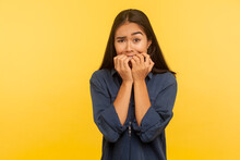 Stress And Anxiety Disorder. Portrait Of Worried Scared Girl In Denim Shirt Biting Nails, Feeling Unsure And Frightened, Worried About Problems. Indoor Studio Shot Isolated On Yellow Background