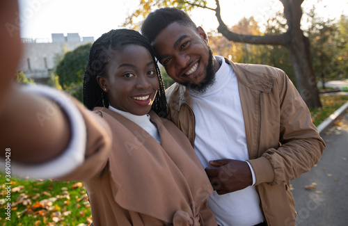 Fotografie, Obraz Cheerful african american couple taking self-portrait while walking in park