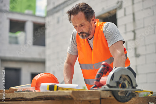 Concentrated serious civil engineer studying construction drawings Slika na platnu