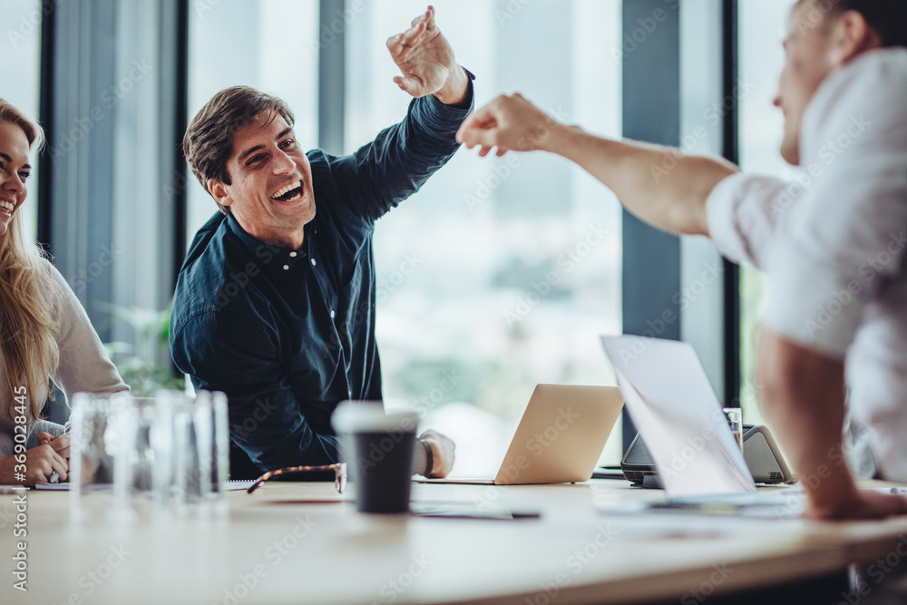 Fototapeta Businesspeople excitedly high fiving together in meeting