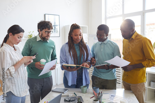 Portrait of contemporary multi-ethnic business team standing around table in office and listening to female African-American leader giving instructions, copy space