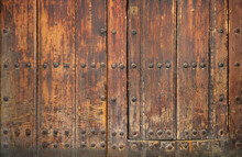 Ancient And Worn Surface Of Wood From An Old Medieval Door With Rivets - Rough Texture Background