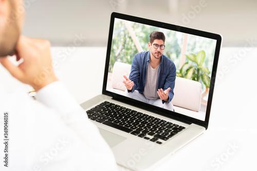 Fototapeta Rear view shot of businessman sitting at desk behind his laptop while having video conference obraz na płótnie