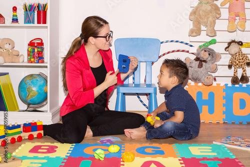 Fototapeta Little boy during lesson with his speech therapist. obraz na płótnie