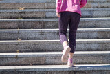 Fototapeta Na drzwi - athlete woman climbing the stairs on the street
