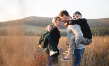 Beautiful Young Family With Small Children On A Walk In Autumn Nature.