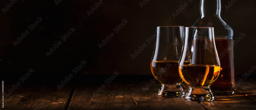 Obraz Scotch Whiskey without ice in glasses and bottle, rustic wood background, copy space banner fototapeta, plakat