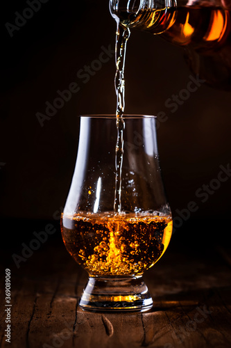 Canvastavla Scotch Whiskey without ice pouring out of the bottle, rustic wood background, co