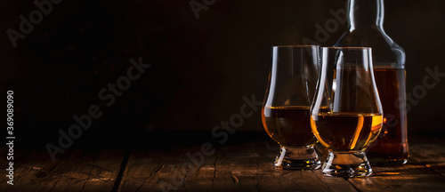 Photo Scotch Whiskey without ice in glasses and bottle, rustic wood background, copy s