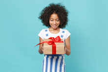 Excited Little African American Kid Girl 12-13 Years Old In Striped Clothes Isolated On Blue Background. International Women's Day Birthday, Holiday Concept. Hold Red Present Box With Gift Ribbon Bow.