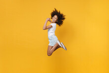 Full Length Portrait Of Smiling Little African American Kid Girl 12-13 Years Old In White T-shirt Isolated On Yellow Wall Background Studio Portrait. Childhood Lifestyle Concept. Jumping, Having Fun.