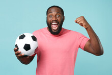 Excited African American Man Guy Football Fan In Pink T-shirt Isolated On Blue Wall Background. Sport Family Leisure Lifestyle Concept. Cheer Up Support Favorite Team With Soccer Ball, Clenching Fist.