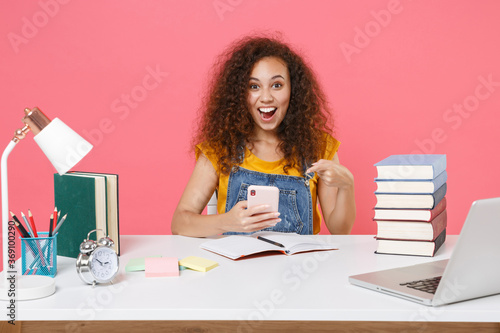 Carta da parati Excited african american girl employee in office sit isolated on pink background