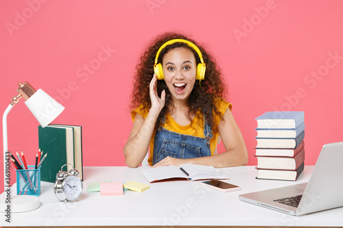 Fotografia Excited african american girl employee in office work at desk isolated on pink background