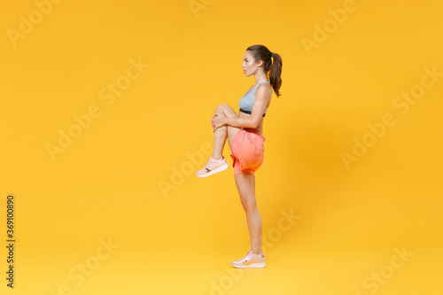 Obraz Full length portrait strong fitness woman in sportswear working out isolated on yellow background. Workout sport motivation lifestyle concept. Mock up copy space. Doing stretching exercising for legs. - fototapety do salonu