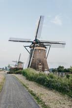 Dutch Windmills Along A Small Path