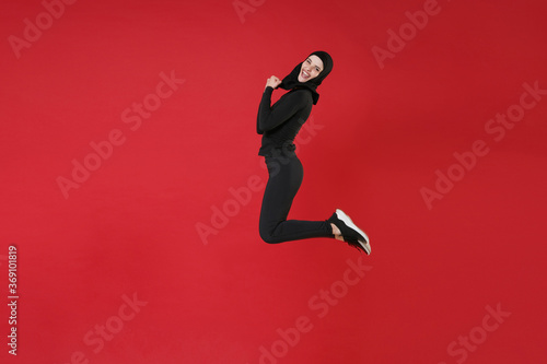 Fotografie, Obraz Full length portrait side view of happy young arabian muslim woman in hijab black clothes posing isolated on red background studio