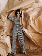 Artistic Woman In Sunglasses Tearing Craft Caper Off Wall