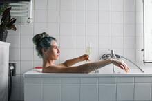 Blue Haired Woman Enjoying A Drink In A Bathtub
